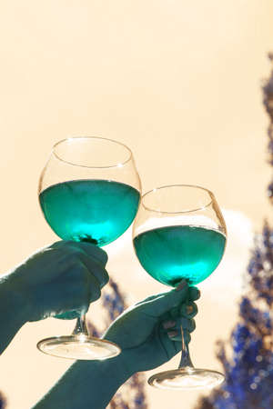 Two glasses with wine in hand against the sky in neon tinted. Mint colour