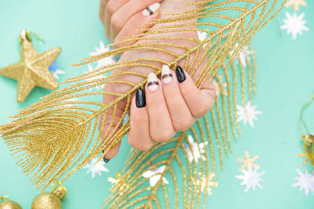 Beautiful female manicure on a colored background with a festive element.