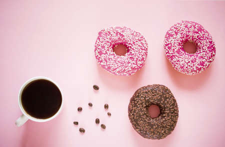 Tasty and delicious donuts with different icing and filling on a colored background with coffee.Donuts on link background