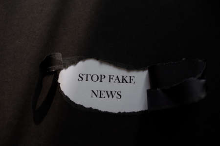 STOP FAKE NEWS printed on a white background with black torn paper.