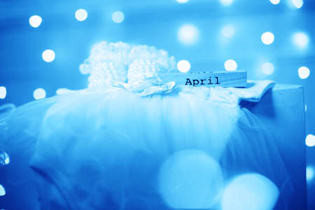 Costume for a newborn girl. Booties, bodik, beautiful bokeh lights. April month and blue toned Stock Photo