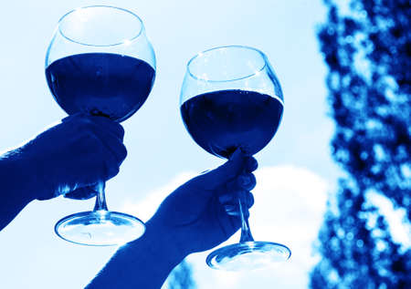 Two glasses with wine in hand against the sky in neon tinted. Pink wine Stock Photo