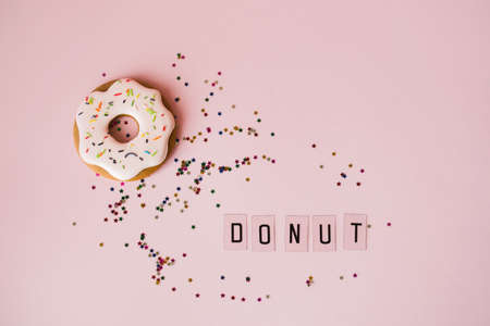 Fragrant gingerbread in the form of doughnuts on a pink background with sequins of small multi-colored stars and donut inscription. Flat lay