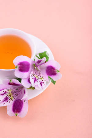 Fragrant tea in a white cup with beautiful flowers on a pink background