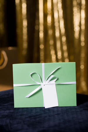 Beautiful packaging for gift in bed tones against the background of a Christmas tree with golden lights. Holidays content 2020