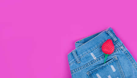 Blue ripped denim shorts on a pink background. In the pocket of the strawberries.
