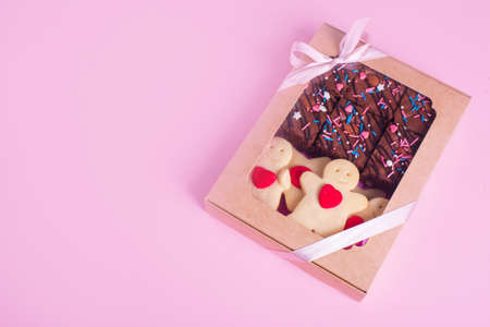 A set of sweets in a box with satin ribbon on the on the pink background. Shortbread cookies with heart, chocolate brownie. Gift cookies.
