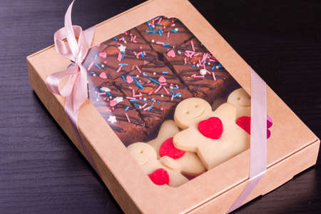 A set of sweets in a box with satin ribbon on the table. Shortbread cookies with heart, chocolate brownie. Gift cookies.