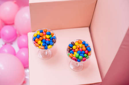 Early-colored round candy in glass glasses. Peanuts in colored chocolate, sweets in a glass. Stock Photo