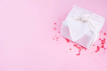 Beautiful little roses, small hearts, hearts of milk chocolate, on a pink background with a beautiful gift of furoshik with white color. Valentines Day. Stock Photo