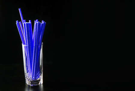 The glass glass on a black background is filled with blue juice tubes. The color of the year.