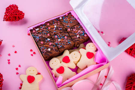 A set of delicious treats in a box with tape. A Valentines Day gift. Pink background, festive concept Stock Photo
