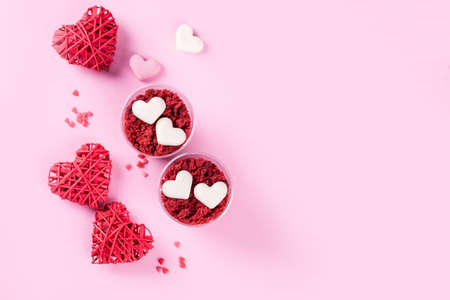 Delicious and beautiful dessert, red velvet in cups. Hearts of white chocolate. Valentines Day, a place for writing on a pink background.