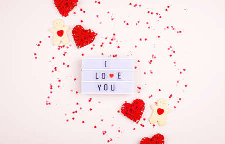 A gentle background with hearts, a gift, a light box and words. Valentines Day. I love you