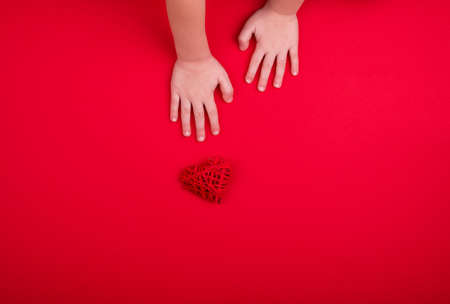 Babys hands hold a small heart on a red background. Place for text.
