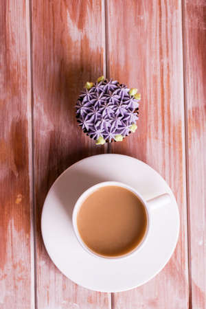 Chocolate delicious cupcake with cream and fragrant coffee with milk on a white wooden table. White dishes for dessert