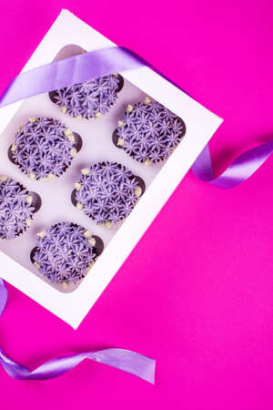 Delicious shawn cupcakes with curd cream in the form of flowers on a pink background. White cupcake packaging.