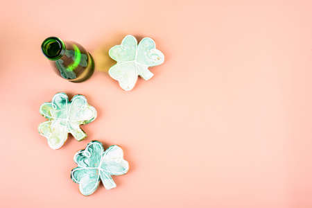 March 17 is St. Patrick's Day. Composition of sweet gingerbread and greeb bottle on a light background. A place for text.