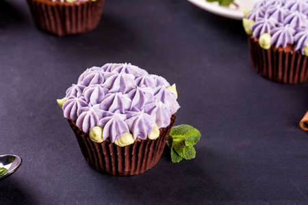 Delicate and beautiful chocolate cupcakes with cream, mint, cinnamon sticks, tea on the table. Tasty food