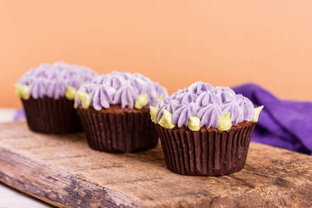 Chocolate cupcakes on a wooden table with salted caramel inside. Dessert, food