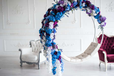 Beautiful decor of a swing of flowers, beautiful two armchairs for a photo. It's a beautiful room with flowers. Imagens - 142517856