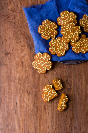 Ginger fragrant cookies in the form of flowers. Delicious cookies with orange juice on a wooden table.