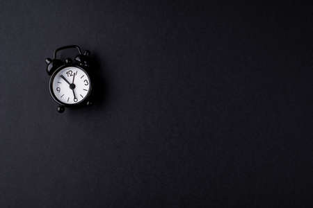 A small black alarm clock on a black background. Abstract content. Place for inscription