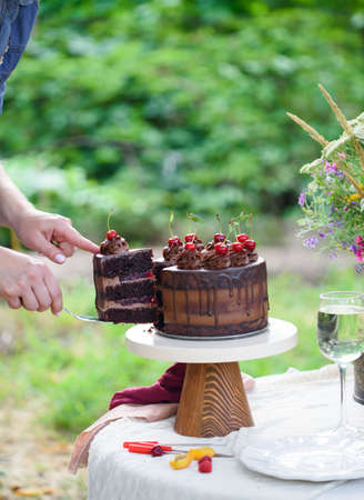 Chocolate cake with cherry on a beautiful bokeh background, with berries and flowers on a summer picnic