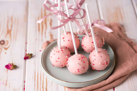 Cake pops in pink cream lie on a beautiful plate. Delicious close-up dessert. Tasty food