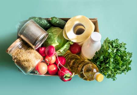 Eine Schachtel mit frischem Gemüse, Lebensmitteln, Müsli, Toilettenpapier, Butter, Kefir, zur Spende auf hellem Hintergrund. Platz für Text Standard-Bild