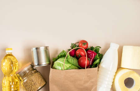 Fresh vegetables, and groceries in a craft bag for purchases. Toilet paper, vegetables, butter, milk, stew, porridge.