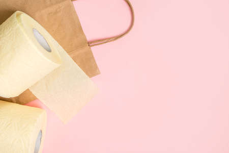 Three rolls of toilet paper with a craft bag for shopping and goods on a pink background. Place for text, view from above. Banque d'images - 146866721