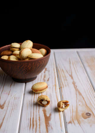 Homemade Russian nuts with condensed milk on a light wooden background, wafer napkin. Cut nuts with condensed milk. Bitten goodies for tea. Condensed Nuts