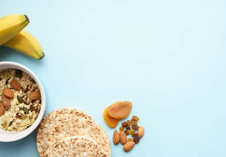 Useful breakfast, proper nutrition, oatmeal, dried fruits, breads, fruits, a centimeter on a light background. Diet. A place for text. Flat lay