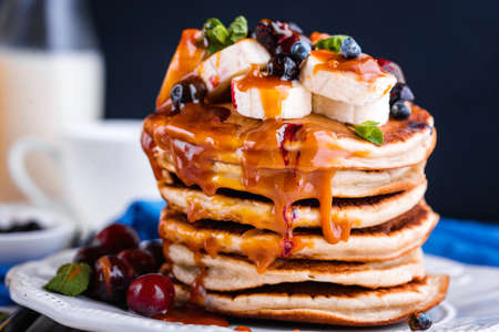 Delicious homemade pancakes with banana, berries, salted caramel, mint, tea. A delicious and healthy breakfast. Фото со стока