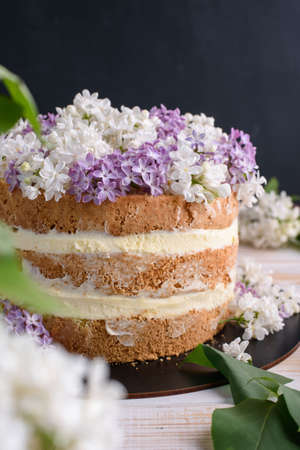 Biscuit cake with cream, impregnated with coconut and pineapple, decorated with lilac flowers. Delicious dessert, food photo.