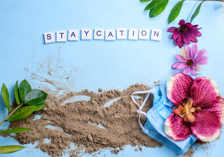 Beach sand on a blue background with wood letters and a word staycation. Holiday at home