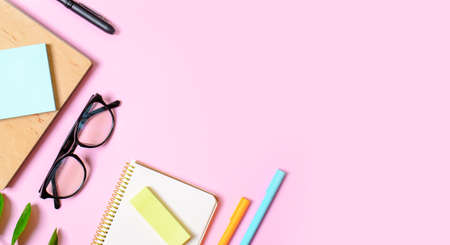 Pink background with notepad, office glasses, pen, place for text. Trend concept. Future