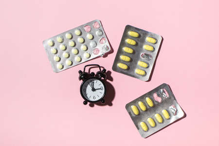 Plates with yolk pills and clocks on a pink background, hard shadows. Health. View from above, place for text