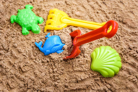 Beach sand with toys for the baby, water, the word summer in colored letters. Staycation content Stockfoto