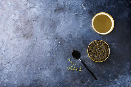 Black sturgeon caviar with a black spoon and a dark background. Seafood, healthy food. Zdjęcie Seryjne