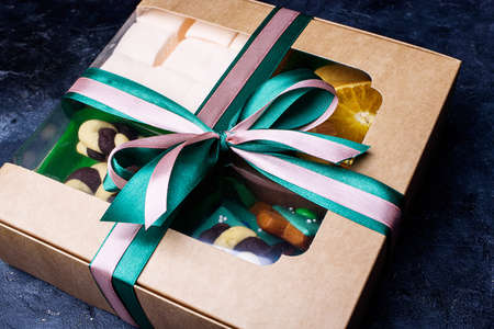 Box with satin ribbons and delicious treats for New Year and Christmas. New Years desserts on a dark background.
