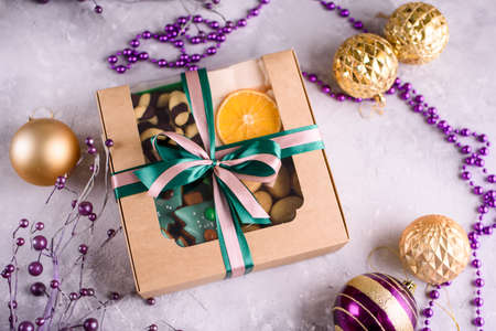 Box with satin ribbons and delicious treats for New Year and Christmas. New Years desserts on a light background.