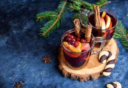 wo glasses of hot red mulled wine decorated with orange, clove, cinnamon and anise. Christmas lights on background. Rustic decor, cozy atmosphere, festive mood. Standard-Bild