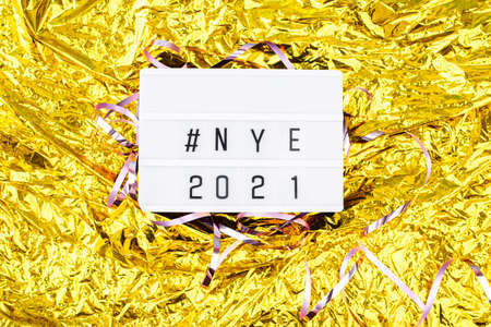Light boxing with the words nye 2021 on a golden background. New Years Eve and content.