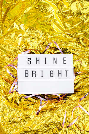 Light boxing with words shine bright on a golden background. New Years content Standard-Bild