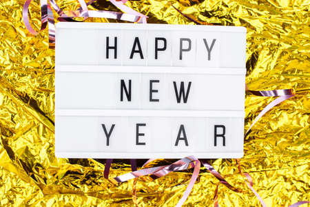 Light boxing with the words happy new year on a golden background. New Years Eve and content. Standard-Bild