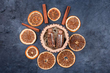 Slices of dried orange, cinnamon sticks, jars of spices for mulled wine. Winter drink