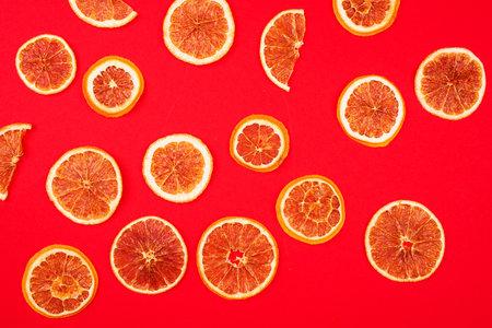 Slices of dried orange on a bright red background. Standard-Bild