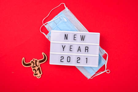 Light box with the inscription New Year, face mask from viruses, watch on a red background. New year 2021 awareness. Standard-Bild